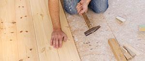 Man op knieën legt houten vloer aan
