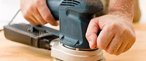 Vloerspecialist met schuurmachine voor renovatie
